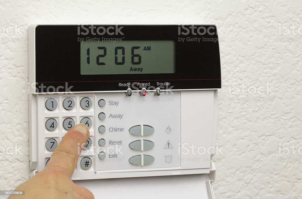 Woman disarming a home alarm royalty-free stock photo