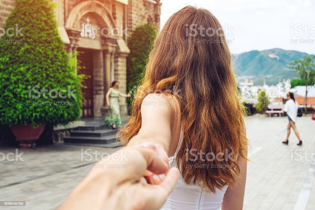 Woman discovering an ancient temple holding boyfriend's hand. stock photo