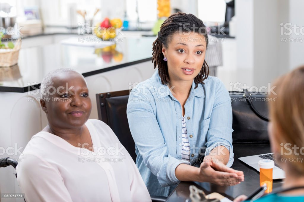 Woman discusses her elderly mom's health with a home healthcare professional stock photo