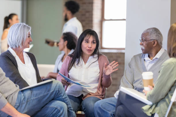 Woman discusses neighborhood issues during HOA meeting Mid adult Hispanic woman gestures as she discusses neighborhood concerns during a homeowner association meeting. group therapy stock pictures, royalty-free photos & images