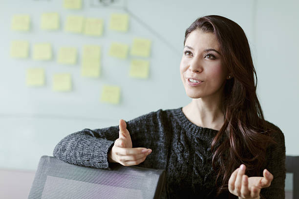 frau diskutiert ideen und strategie im studiobüro - gestikulieren stock-fotos und bilder