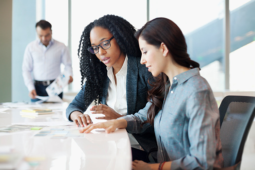 istock Woman discussing ideas with coworkers in office meeting 1148560161