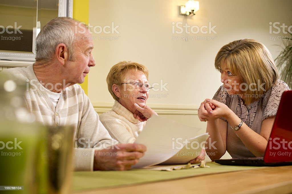 A woman discussing paperwork at a table with an older couple stock photo