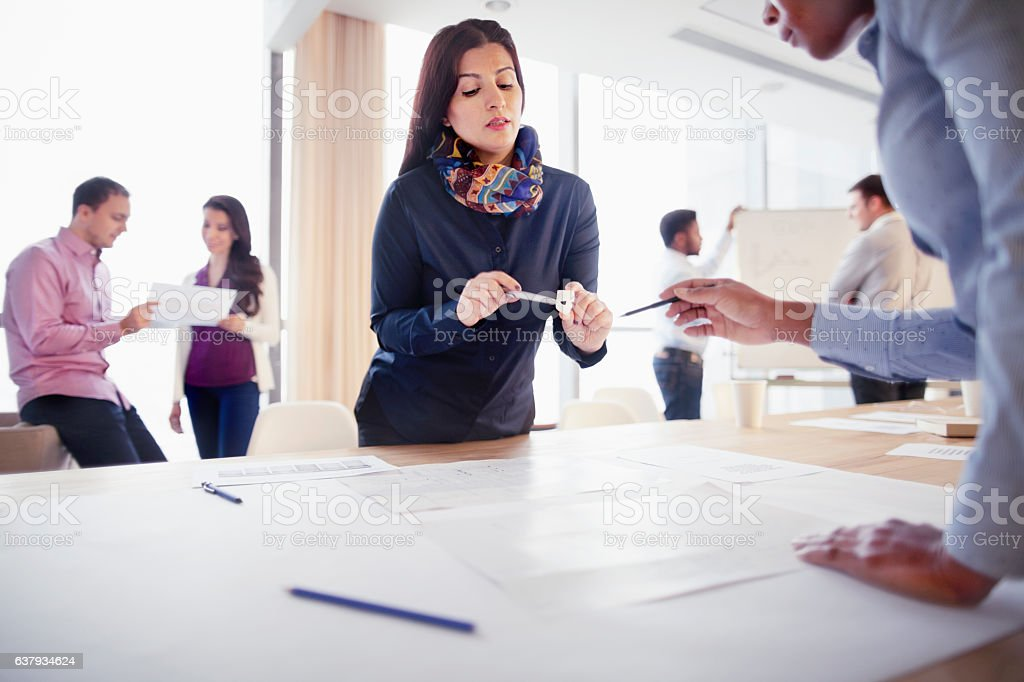 Woman discussing part design with colleague in innovation studio stock photo