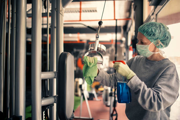 Woman disinfecting and cleaning gym stock photo
