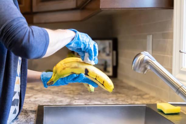 Frau desinfiziert Lebensmittel und Früchte während Covid-19 Krise zu Hause – Foto