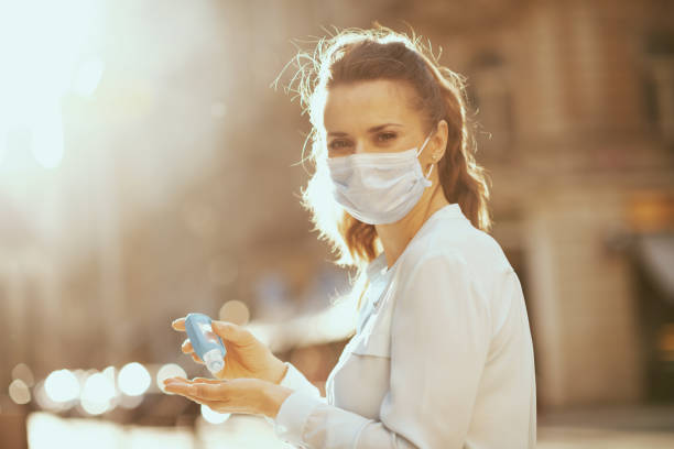 woman disinfecting hands with sanitizer outdoors in city stock photo
