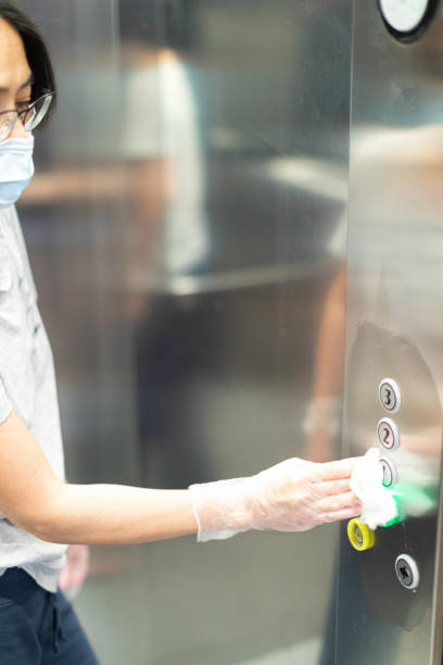 Woman disinfecting with a wipe the buttons of an elevator during Covid-19 stock photo