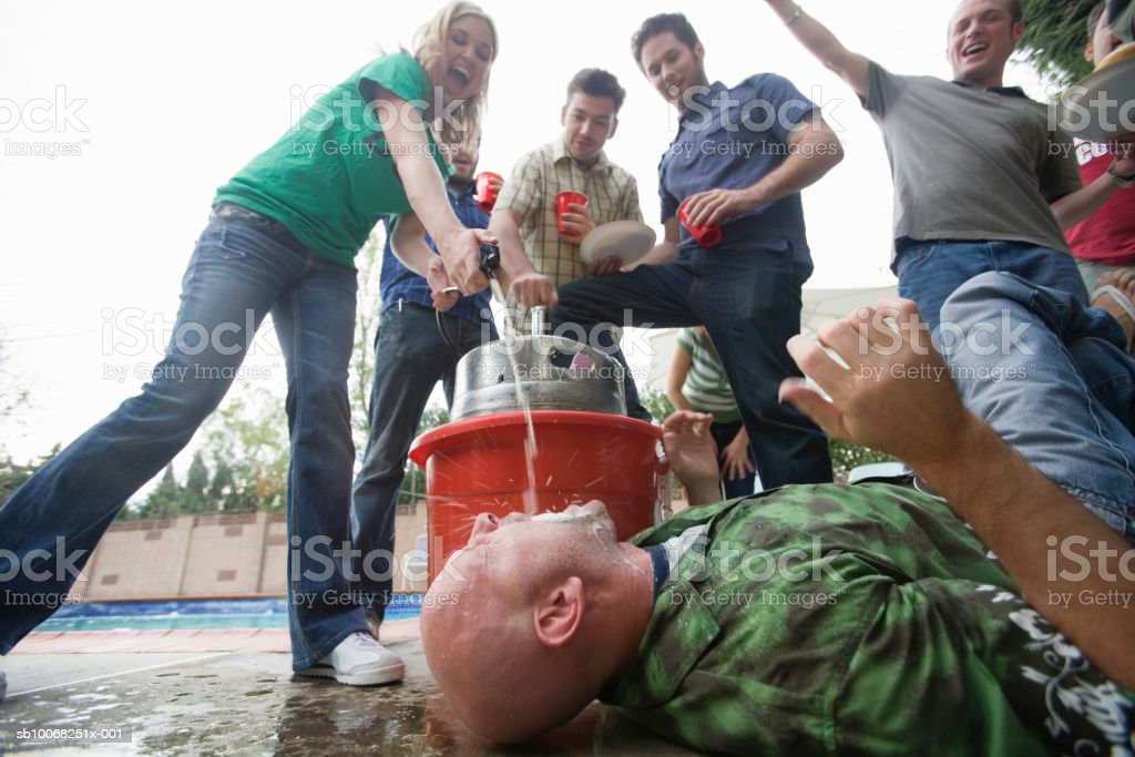 Woman dispensing beer directly from keg into mouth of man lying on ground royalty-free stock photo