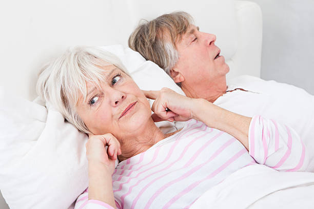 Woman Disturbed With Man Snoring Portrait Of Senior Angry Woman Awaken By Her Husband Snoring inconvenience stock pictures, royalty-free photos & images