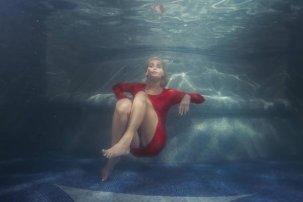 woman dives under the water. - frau tiefer ausschnitt stock-fotos und bilder