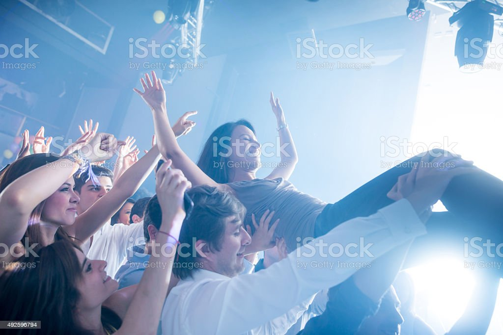 Woman diving into the crowd at a concert stock photo
