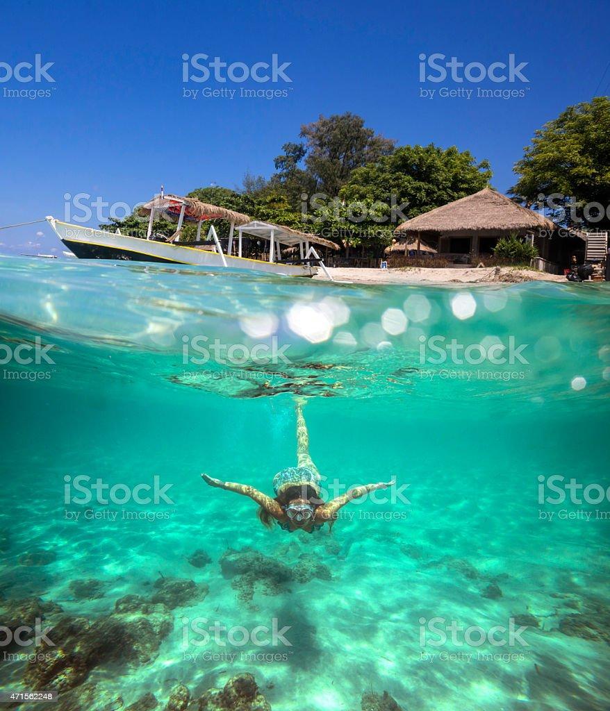 Woman diving near tropical island stock photo
