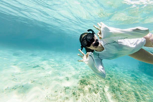 Woman Diving Underwarter Signing OK to the Camera - foto de acervo