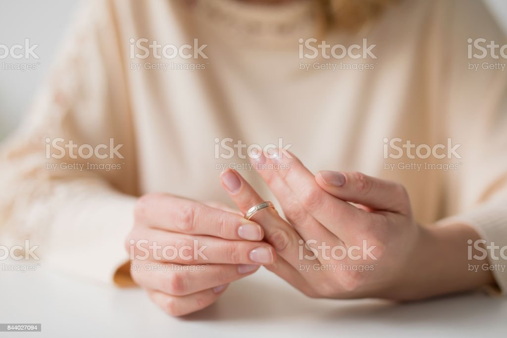 Woman divorcing and taking off wedding band stock photo