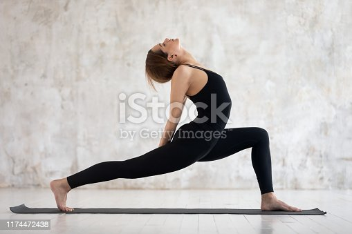 Side view grace woman in black sportswear perform yoga exercise against textured beige grunge studio wall girl do Horse Rider Anjaneyasana asana, improvement of body shape, healthy life habits concept