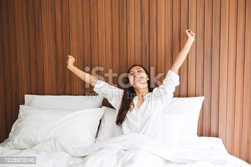 istock woman do stretching after waking up in the morning on a white cozy bed at home 1223920240