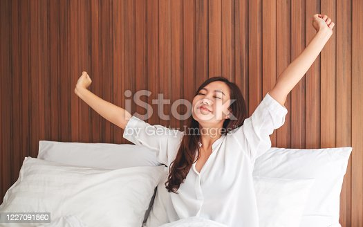 istock woman do stretching after waking up in the morning on a white cozy bed at home 1227091860