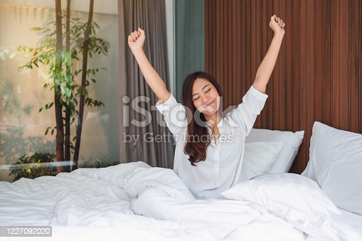 istock woman do stretching after waking up in the morning on a white cozy bed at home 1227092020
