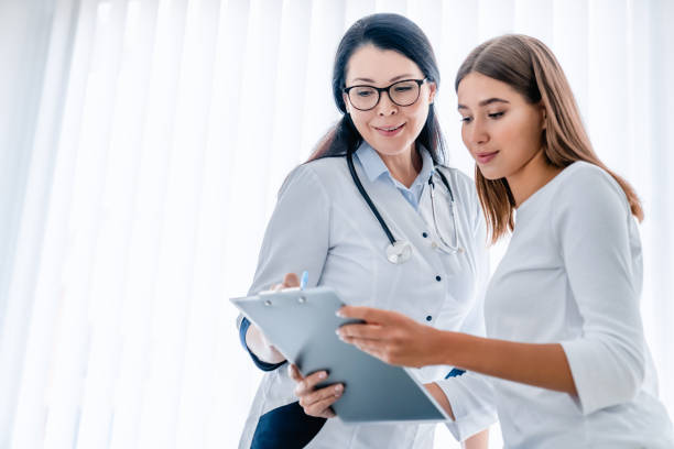 Woman doctor and her patient looking at tablet together and discussing Medicine, Hospital, Medical Clinic, Doctor, Patient female doctor stock pictures, royalty-free photos & images