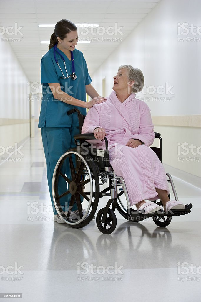 Woman Doctor Helping Woman Patient in Wheel Chair royalty-free stock photo