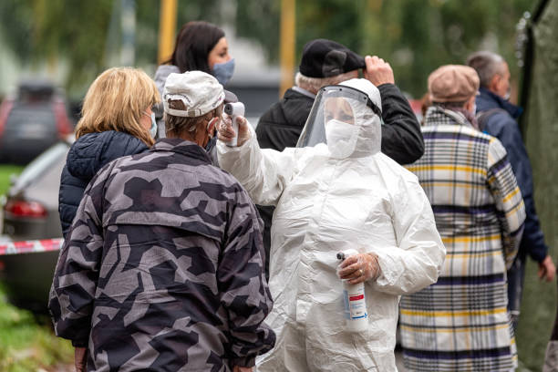 Woman doctor in protective suit and shield checked a temperature of people with thermometer. stock photo