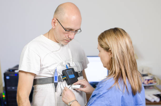 Woman doctor installing sleep apnea monitor on a man patient