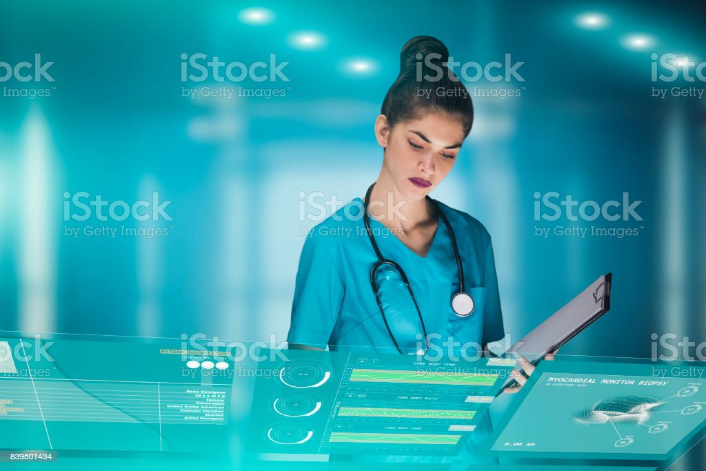 woman doctor or nurse futuristic concept, that is using a holographic medical workstation panel in order to monitor health data of a patient in the hospital, advertising image with copy space stock photo