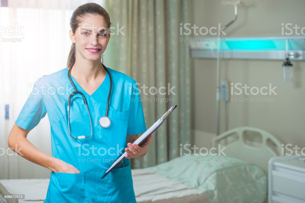 woman doctor or nurse standing in hospital room stock photo