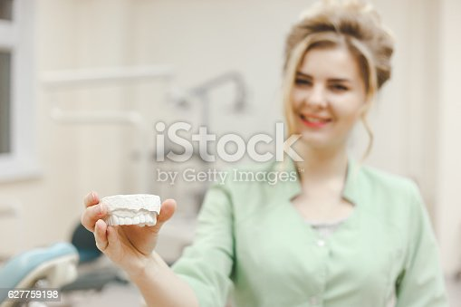 istock Woman doctor orthodontist shows a plaster cast of the upper 627759198
