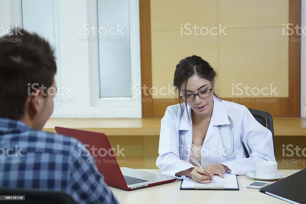 Woman doctor talking to her male patient at office royalty-free stock photo