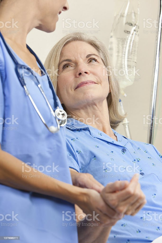 Woman doctor treating senior female patient in hospital bed stock photo