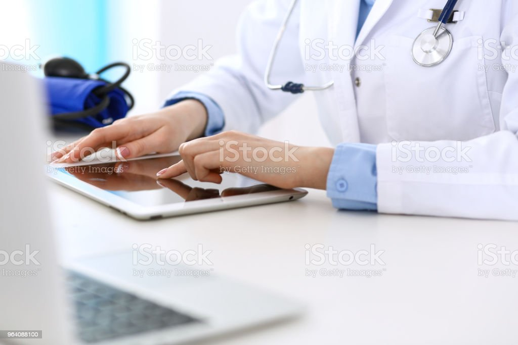 Woman doctor using tablet computer while sitting at the desk in hospital closeup. Cardiologist checks heart diagrams with tablet pc. Healthcare, insurance and smart technology in medicine concept - Royalty-free Adult Stock Photo