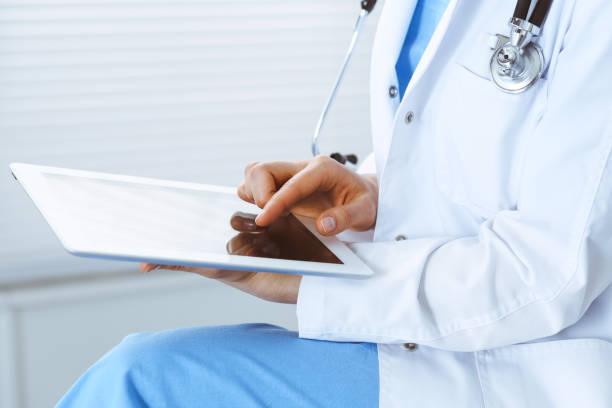 Frau Arzt mit weißen Tablet-Computer, während sitzen auf dem Stuhl im Krankenhaus, Nahaufnahme – Foto