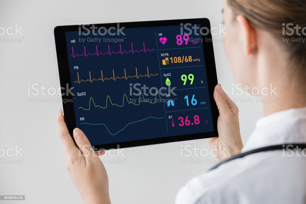 Woman doctor watching vital sign with tablet PC. stock photo