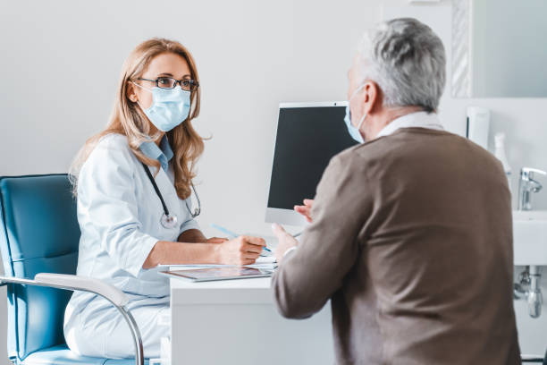 Woman doctor wear protection face mask talking with patient in clinic office Woman doctor wear protection face mask talking with patient in clinic office general practitioner stock pictures, royalty-free photos & images