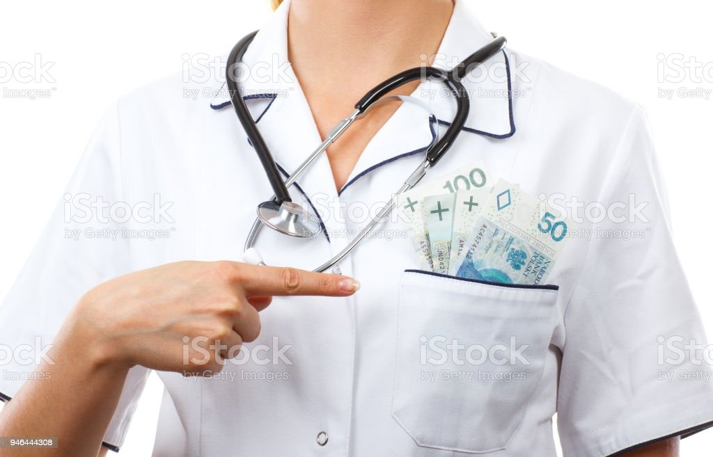 Woman doctor with stethoscope showing polish money in apron pocket, corruption, bribe or paying for care concept stock photo