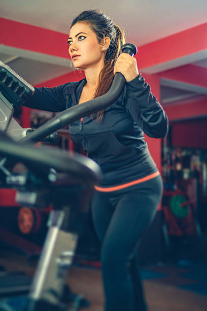 Woman does cardio exercise on elliptical cross-trainer in a gymnasium. stock photo