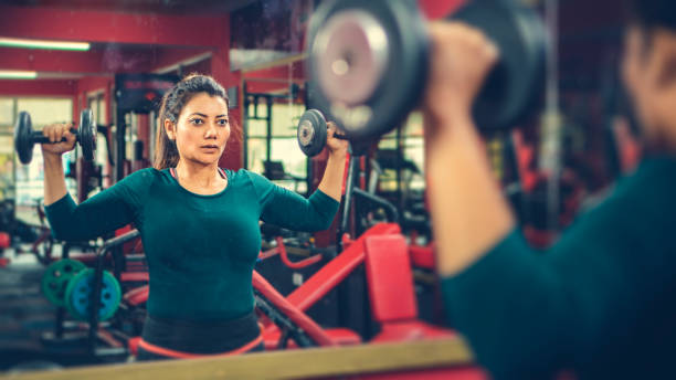 Frau macht Hantel-Training in einer Turnhalle. – Foto