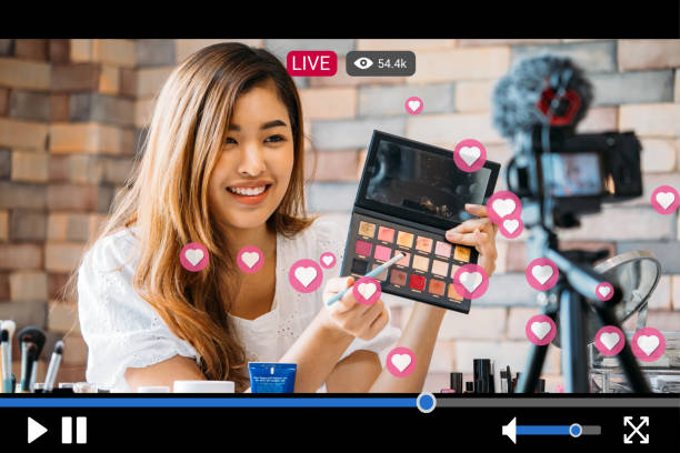 Frau macht Make-up während der Aufnahme von Live-Stream mit Video-Player-Schnittstelle – Foto