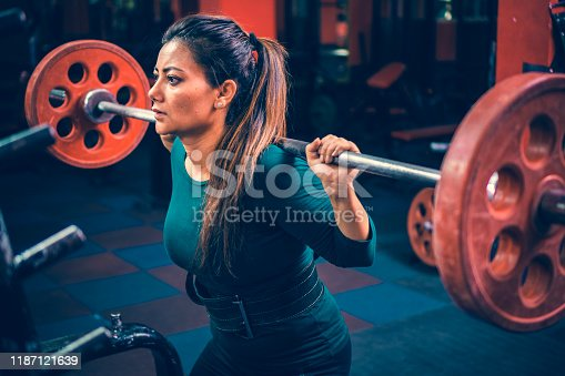 Indoor image of an Asian/Indian, mid-adult woman does squats workout with a barbell in a gymnasium for her fitness.