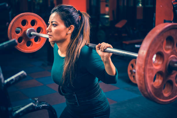 Woman does squats workout with a barbell in a gymnasium for fitness. stock photo