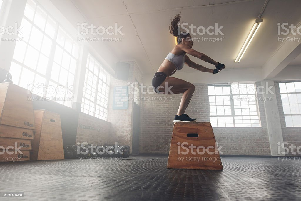 Woman doing a box squat at the gym stock photo