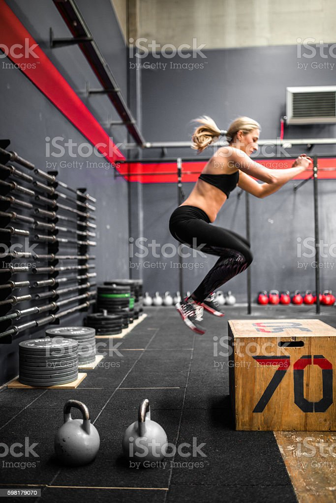 woman doing a box squat on the gym stock photo