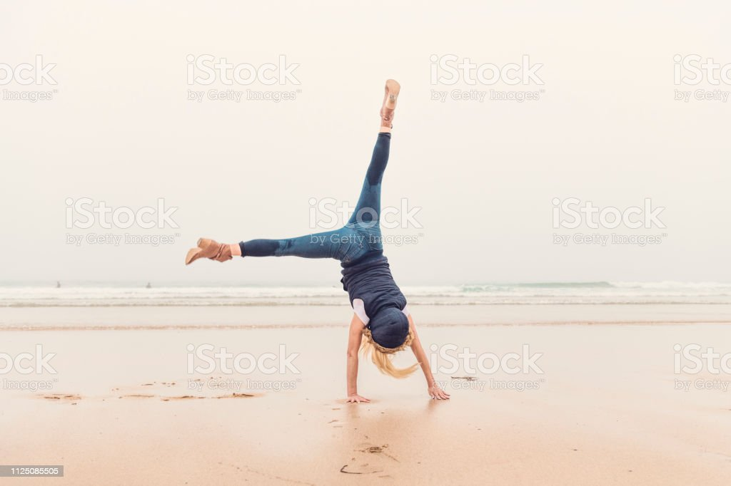 Woman doing a cartwheel handstand at Fistral Beach, Newquay, Cornwall on an Autumn day. stock photo