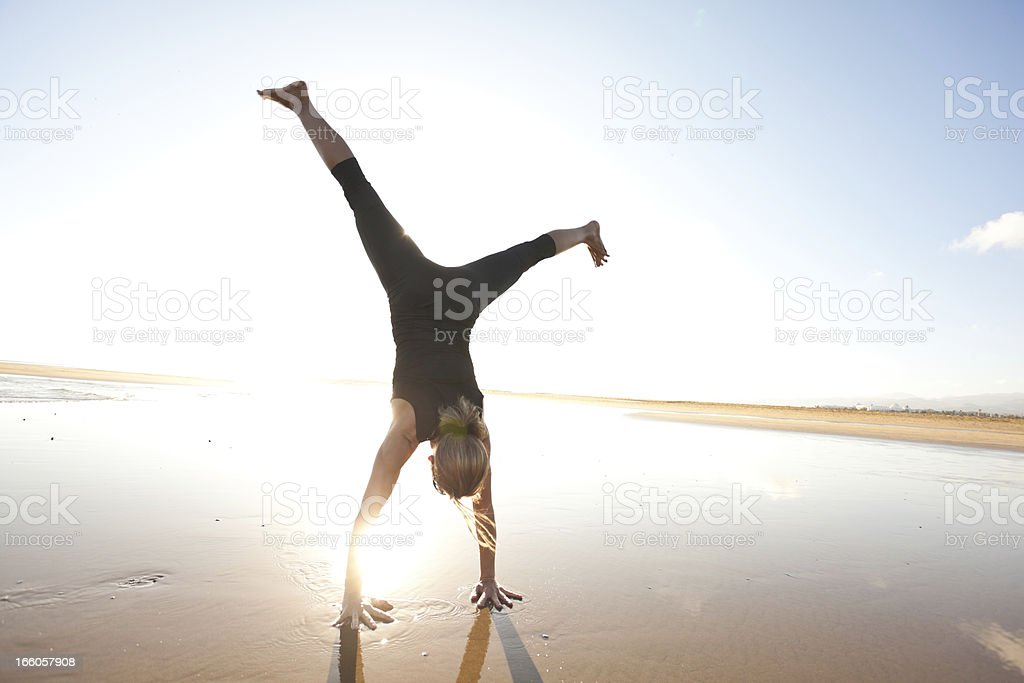 woman doing a cartwheel on the beach stock photo