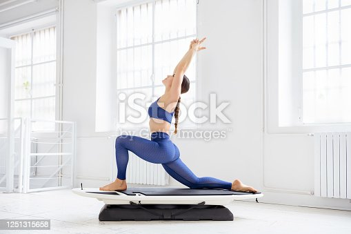 Young woman doing a surf set yoga crescent moon pose on a board or fitness surfer in a high key gym in profile in a health and fitness concept