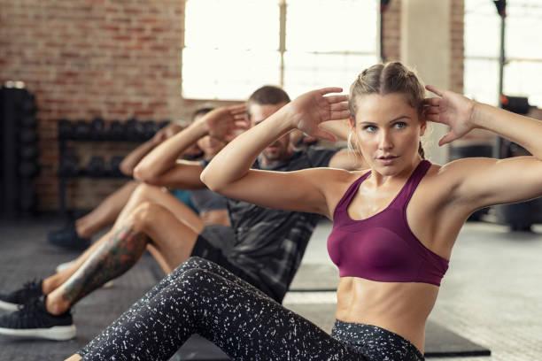 woman doing abs exercise at cardio course - class стоковые фото и изображения