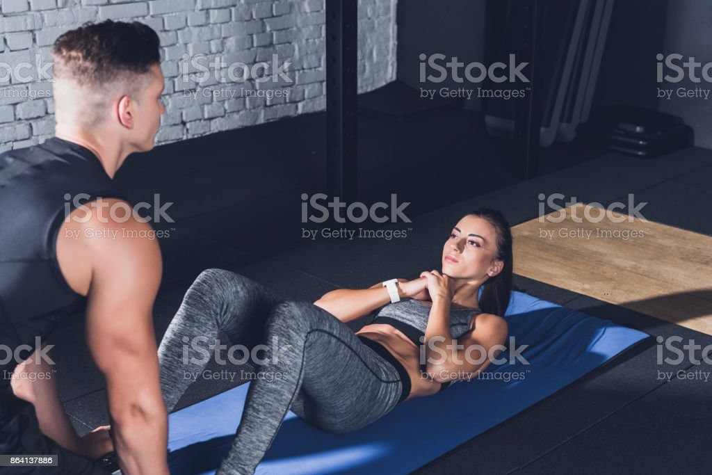 woman doing abs exercises with trainer royalty-free stock photo