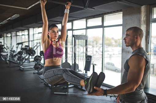 Woman doing abs workout on horizontal bar with personal trainer